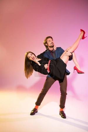 boyfriend holding girlfriend on arms
