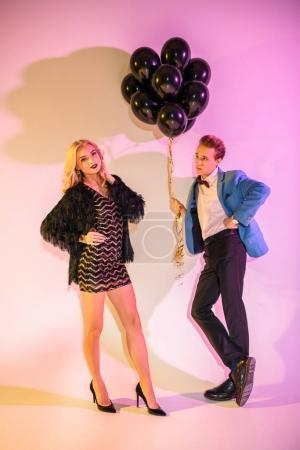 Photo pour Jeune couple élégant, posant avec des ballons noirs sur rose - image libre de droit