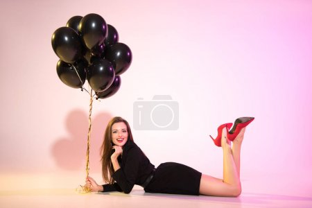 woman lying with black balloons