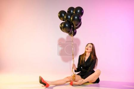 woman sitting with black balloons