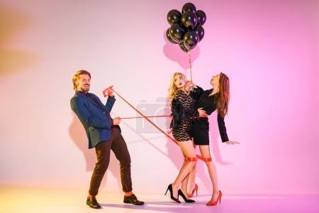 man holding girls bound with ribbon