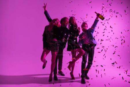 Photo for Silhouette of stylish friends having fun with champagne bottle and confetti, on pink - Royalty Free Image