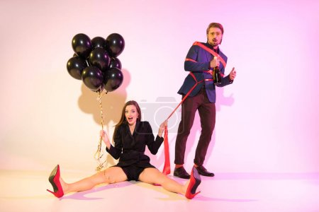 Photo for Young glamorous girl with black balloons holding man bound with red ribbon, on pink - Royalty Free Image