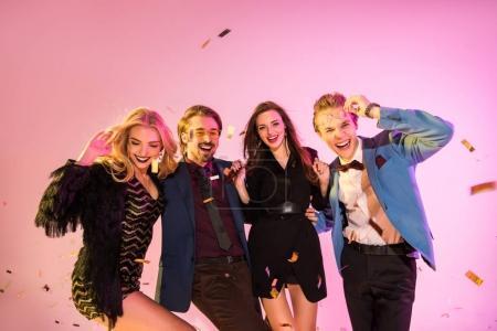 Photo pour Joyeux amis glamours s'amuser sur la partie avec des confettis, rose - image libre de droit