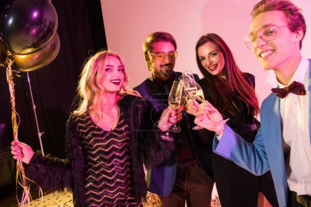 Photo for Happy fashionable friends clinking with champagne glasses having fun on party, on pink - Royalty Free Image