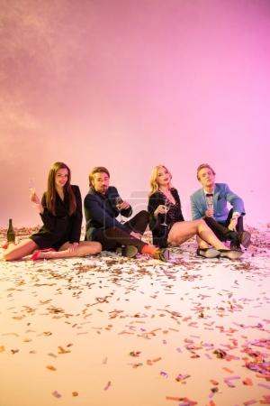 fashionable friends on floor with confetti