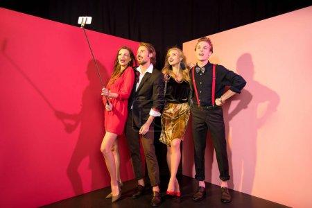 Foto de Amigos glamorosos felices tomando selfie en teléfono inteligente en el estudio - Imagen libre de derechos