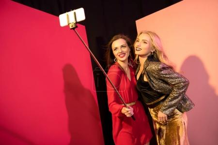 Photo for Happy glamorous girls taking selfie on smartphone and posing in studio - Royalty Free Image