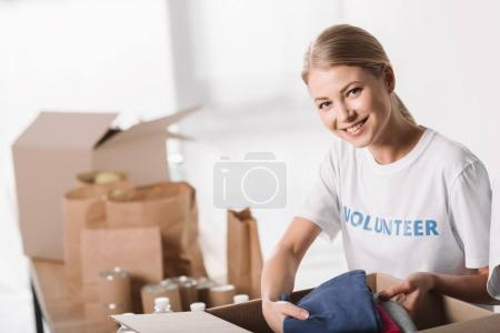 female volunteer putting clothes into box