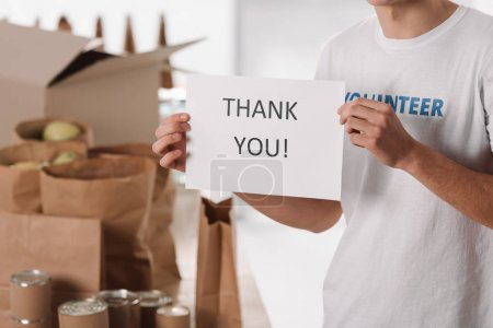 volunteer with thank you placard
