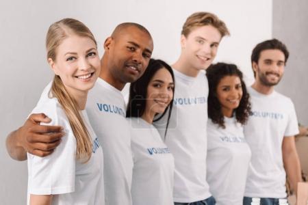 Photo pour Groupe multiethnique de bénévoles permanent en ligne et d'embrasser - image libre de droit