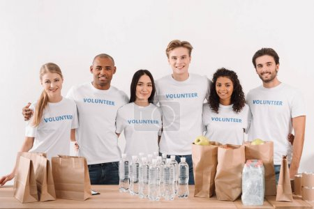 Photo for Multiethnic group of volunteers embracing next to table with charity stuff - Royalty Free Image