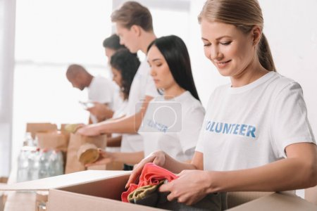 volunteer putting clothes into box