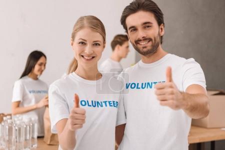 Photo pour Jeune souriant couple volontaires montrant le pouce vers le haut - image libre de droit