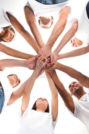 Photo for Bottom view of multiethnic group of volunteers making team gesture isolated on white - Royalty Free Image