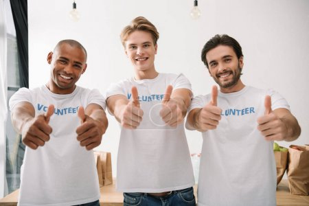 Photo for Group of multiethnic volunteers showing thumbs up - Royalty Free Image