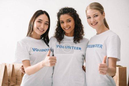Photo pour Groupe de joyeux femmes volontaires montrant les pouces vers le haut - image libre de droit
