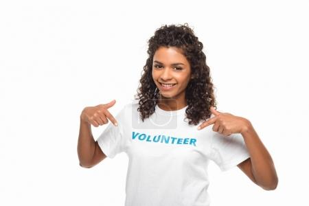 volunteer pointing at sign on t-shirt