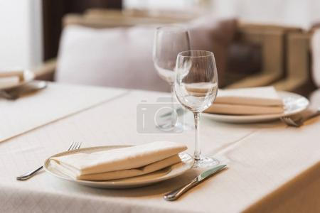 Photo for Served table with wineglasses, plates with napkins and cutlery - Royalty Free Image