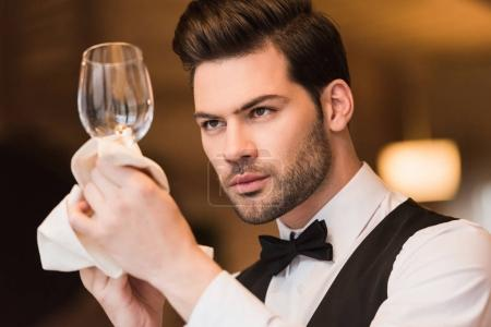 waiter looking at clean wineglass