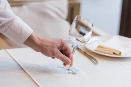 waiter putting empty wineglass on table