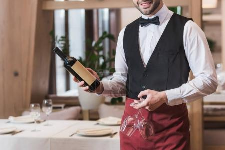 Photo for Cropped image of smiling waiter holding bottle of red wine and two wineglasses - Royalty Free Image