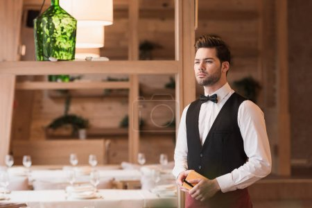 Waiter standing with notebook and pen