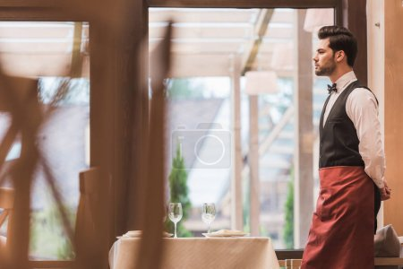 waiter standing near empty table