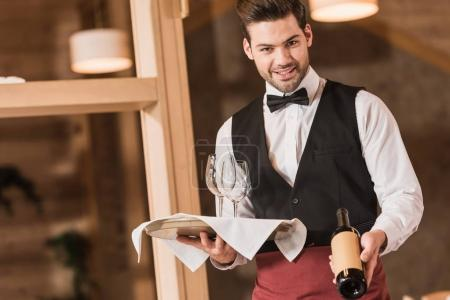 Waiter holding wineglasses and bottle