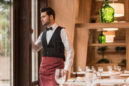 Waiter looking at window