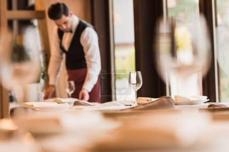 Photo for Waiter serving tables at the restaurant with wineglasses on blurred foreground - Royalty Free Image