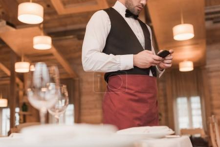Photo for Cropped image of waiter standing and looking at smartphone - Royalty Free Image