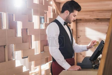 Waiter standing at cash register