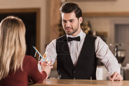 bartender giving cocktail to client