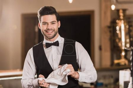 Photo for Smiling Bartender cleaning wineglass with white rag - Royalty Free Image