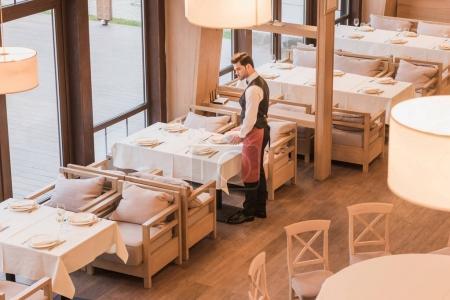Photo pour Beau serveur servant des assiettes sur une table dans un restaurant vide - image libre de droit