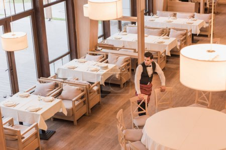 Waiter putting chairs around table