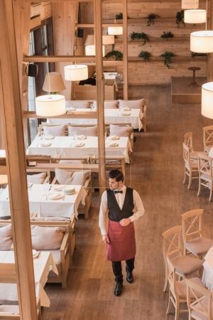 Waiter going between empty tables