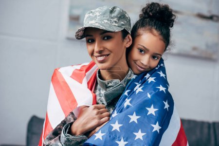 daughter and soldier wrapped with american flag