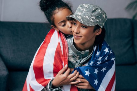 daughter kissing mother in military uniform