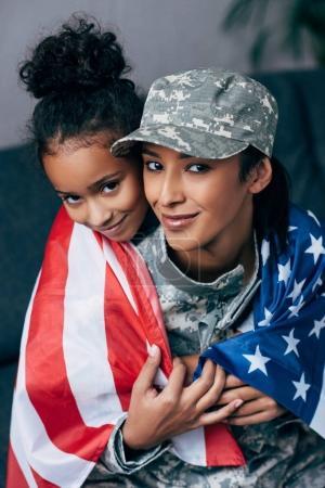 Photo pour Sourire de fille afro-américaine et femme soldat en uniforme militaire, enveloppé d'un drapeau américain à la maison - image libre de droit