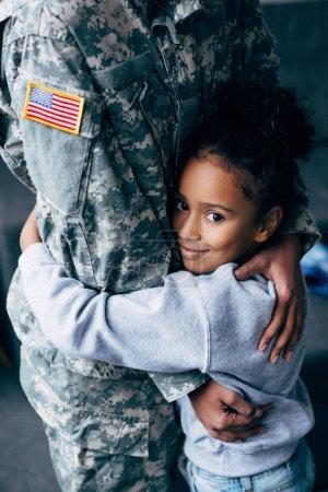 Photo pour Vue recadrée de la fille afro-américaine étreignant soldat féminin en uniforme militaire à la maison - image libre de droit