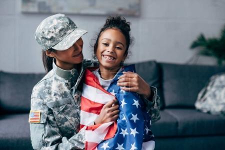 Foto de Hija americana africano envuelta con la bandera americana y mujer soldado en uniforme militar - Imagen libre de derechos