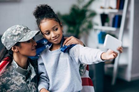 Photo pour Soldat afro-américain en uniforme militaire et fille prenant selfie sur smartphone - image libre de droit