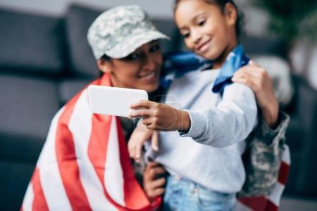 daughter and soldier with flag taking selfie