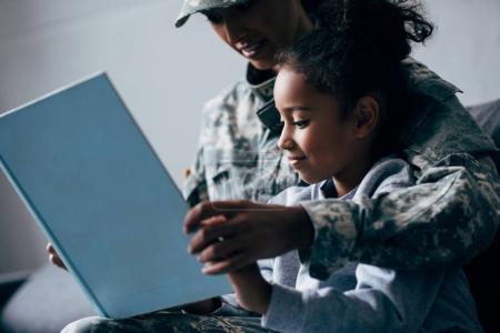 Photo pour Afro-américaine fille et mère en uniforme militaire livre de lecture ensemble à la maison - image libre de droit