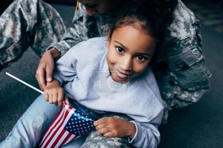 Photo for African american daughter and female soldier in military uniform with american flag at home - Royalty Free Image