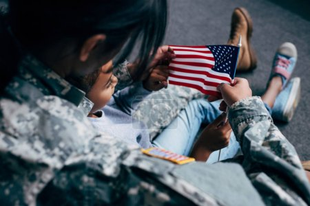 daughter and soldier with american flag