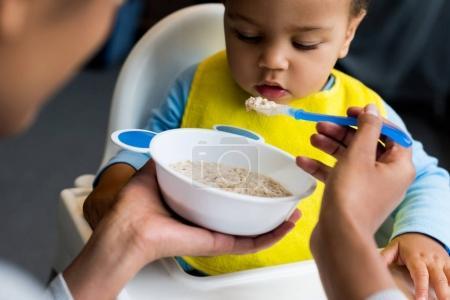 little son eating porridge