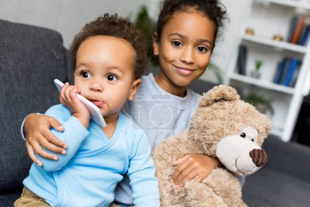 siblings with smartphone and teddy bear